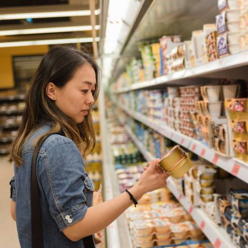 Woman reading yoghurt label in supermarket