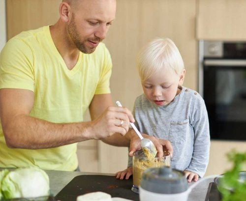 Father and young son making homemade dip/hummus