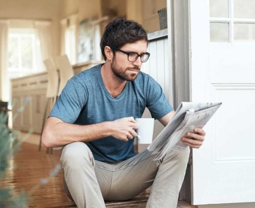 Man drinking coffee and reading a newspaper