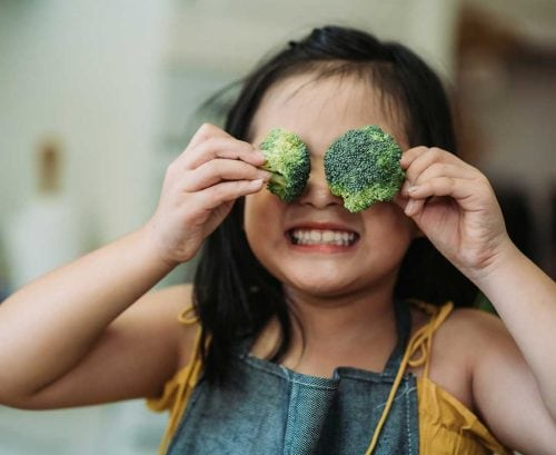 Young healthy girl with broccoli in her eyes