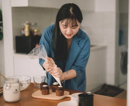 Woman mindfully icing cupcakes