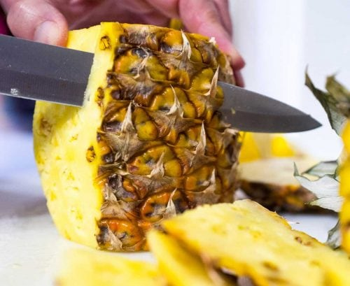Person cutting up pineapple