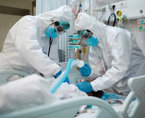 Medical staff in PPE intibating COVID patient