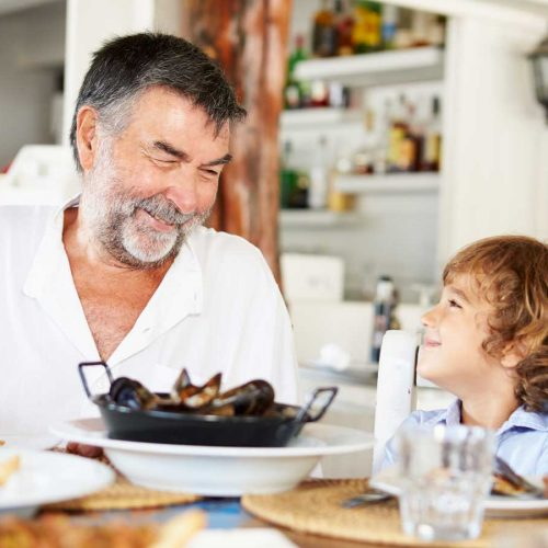 Grandfather and grandchild eating mussels