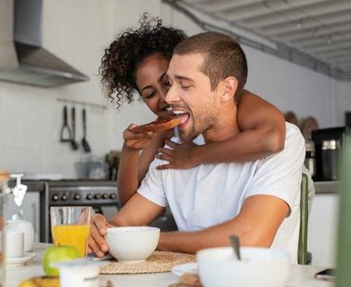 woman feeding wholegrain toast to her boyfriend