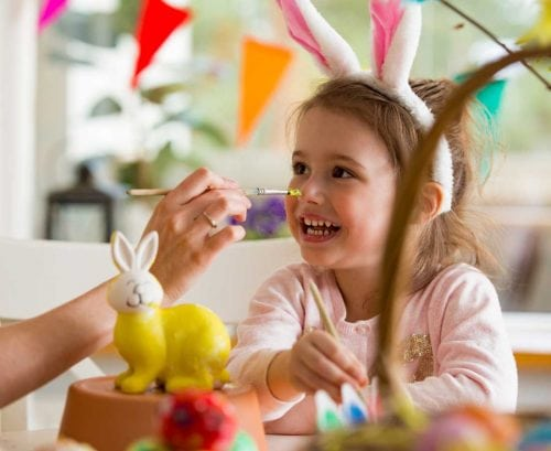 Girl with Easter bunny ears on making crafts