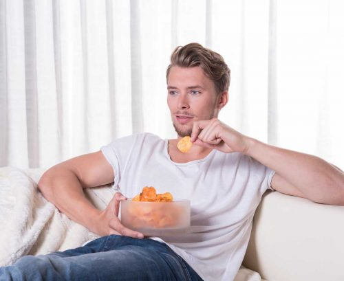 Man eating salty chips or crisps