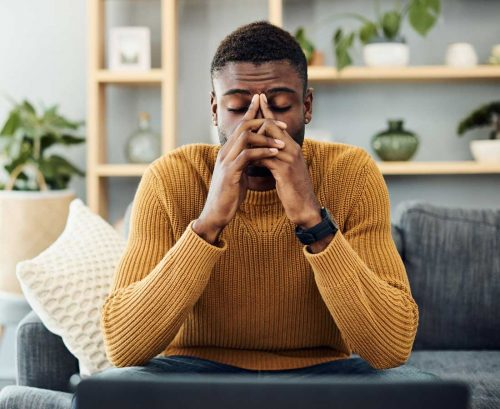 Man sitting on couch looking stressed