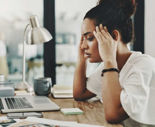 Woman at her desk looking burnt out