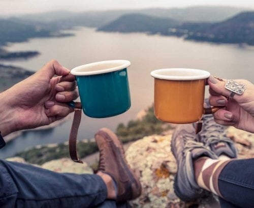 Man and woman drinking tea in front of view from mountain