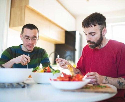 Two men eating lighter bolognese
