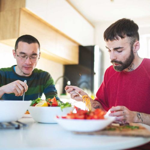Two men eating lighter bolognese
