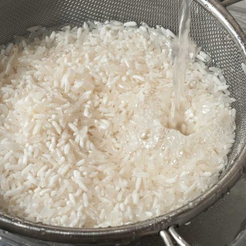 Rinsing white rice with water