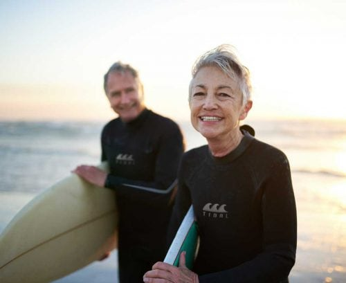 Healthy older couple with surfboards