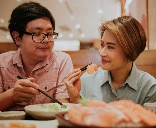 Couple eating salmon sashimi