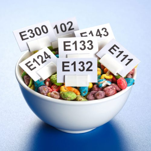 Bowlful of colourful cereal with E-name tags for various food additives