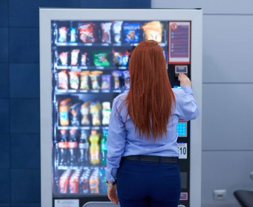 Person choosing snacks from a vending machine