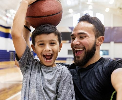 Happy father and son playing with a basketball