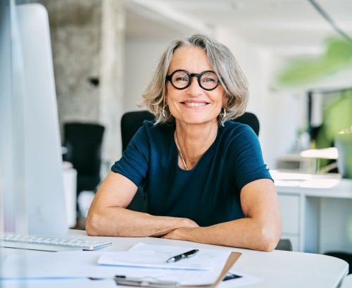 Happy older professional woman wearing glasses smiling from behind her computer