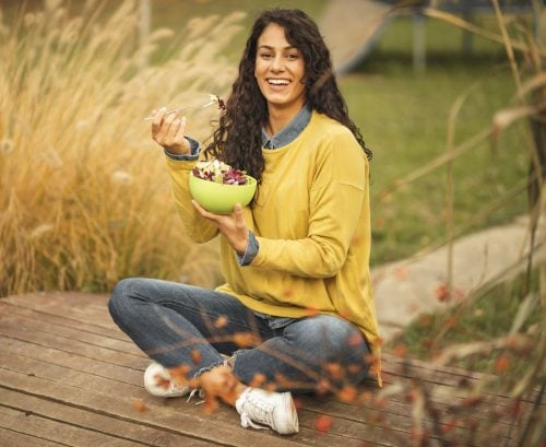 Woman eating a plant-based meal, sitting crossed legged outside