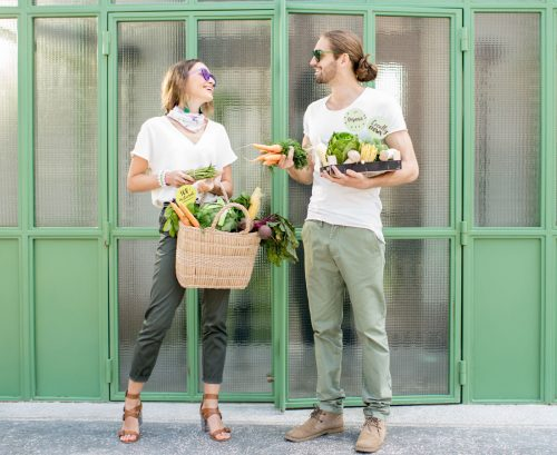 vegan couple standing together with their grocery shopping