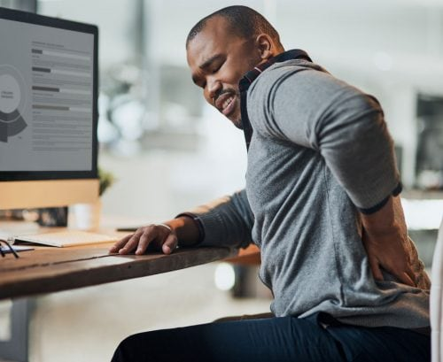 Man at his computer with back pain