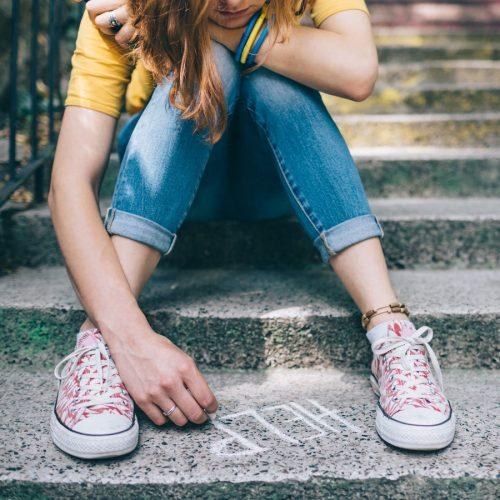 Sad teen girl writing 'help' on pavement
