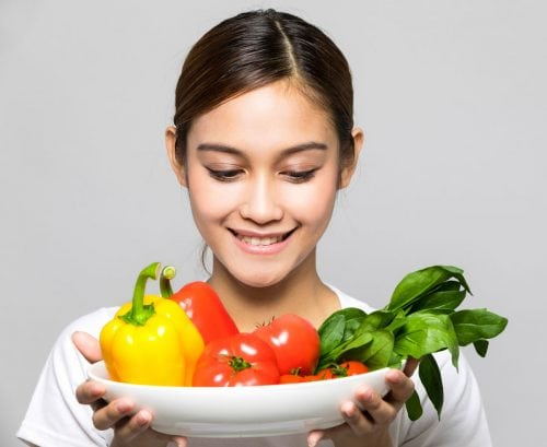 Teenage girl smiling at a plate of vegetables