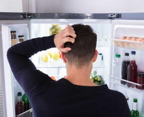 Man staring at fridge deciding what to eat