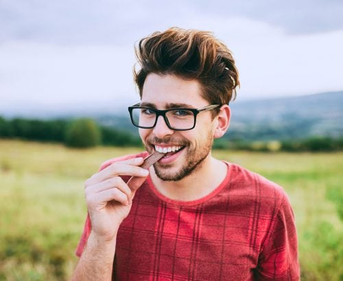 Young man eating chocolate in a field