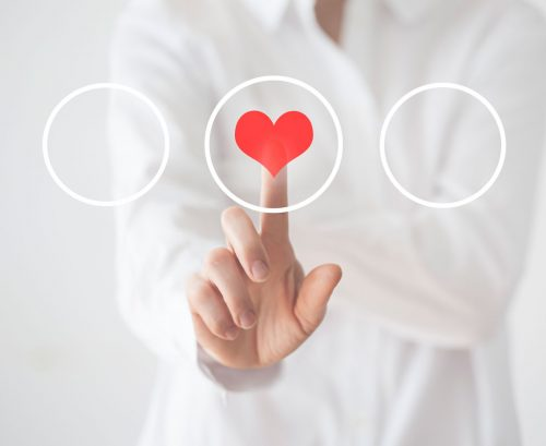 person touching a heart graphic on a perspex screen