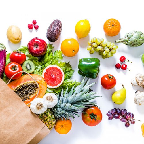 Grocery bag spilling an array of fruit and vegetables