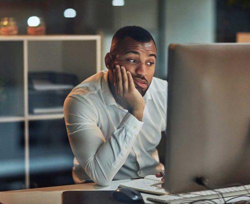 Man at computer looking tired