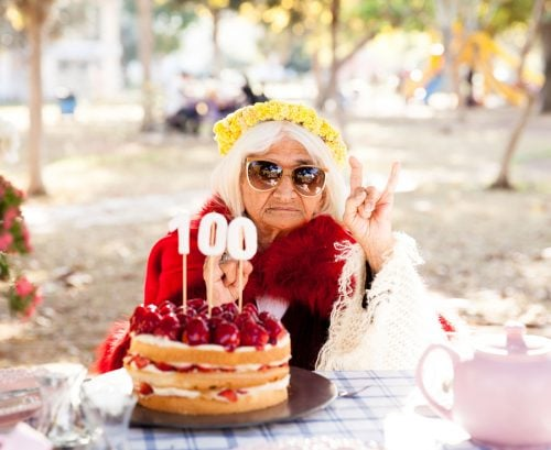Woman in sunglasses celebration 100th birthday with cake