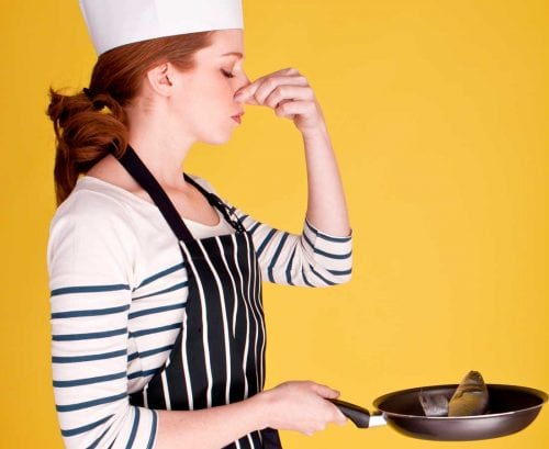 Woman with a fish in a frying pan, holding her nose