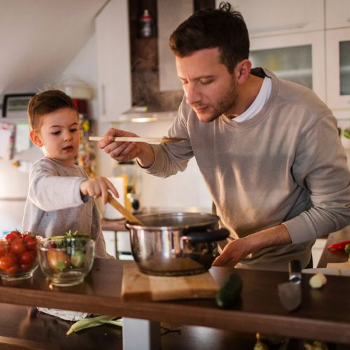Man cooking with young son