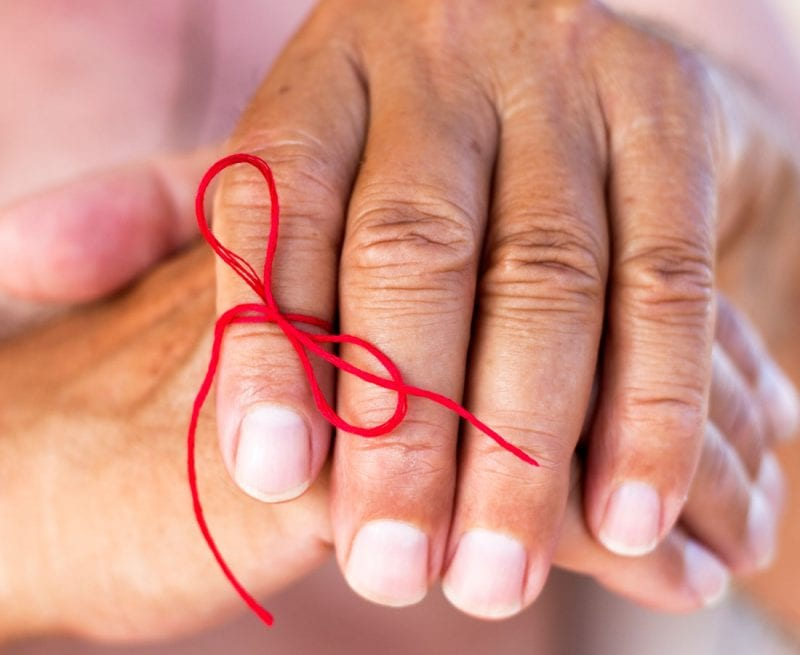 Older person's hand with a bow tied around a finger to remind them not to forget