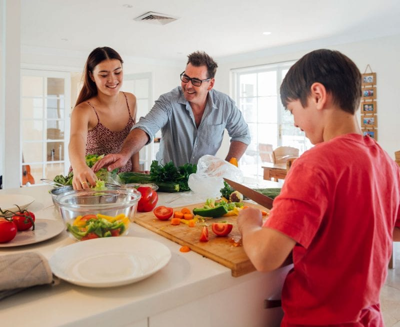 Ftaher and daughter and son preparing a healthy meal, looking happy