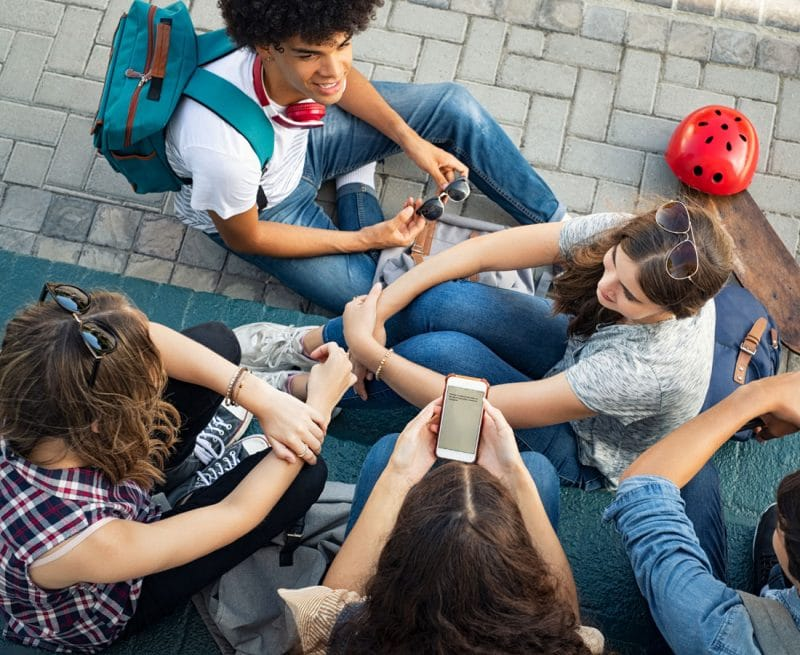 A group of teens sitting on the ground