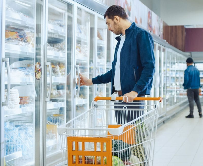 Man choosing frozen meal in supermarket freezer