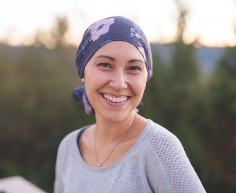 Woman with scarf on her head smiling at camera
