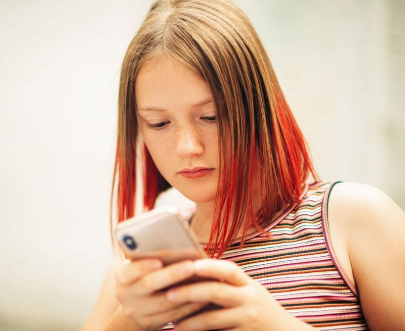 Adolescent girl looking at phone