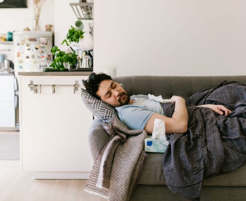 Man lying on couch feeling sick