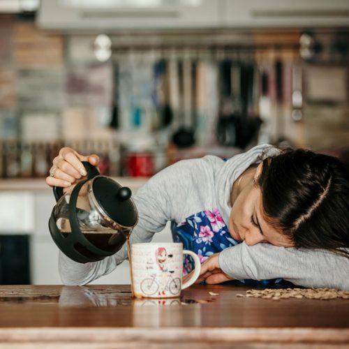 Tired woman puring coffee into an overflowing cup