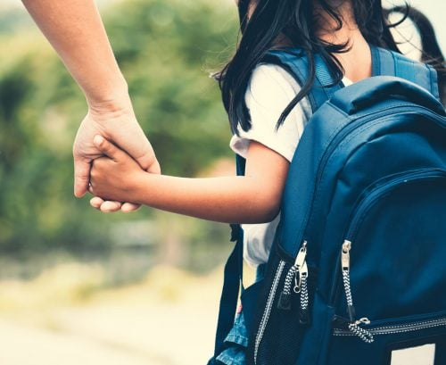 Primary school child walking to school holding mother's hand