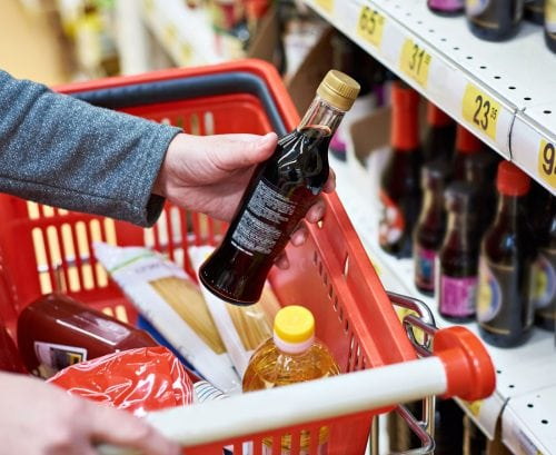 Person putting soy sauce in shopping trolley