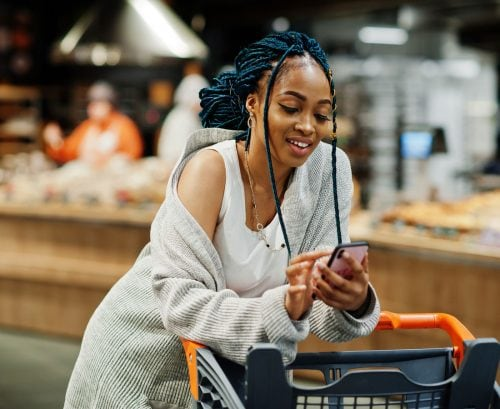 Woman using her smartphone at the supermarket